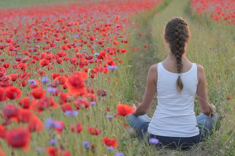 Woman doing yoga in a field of poppy flowers